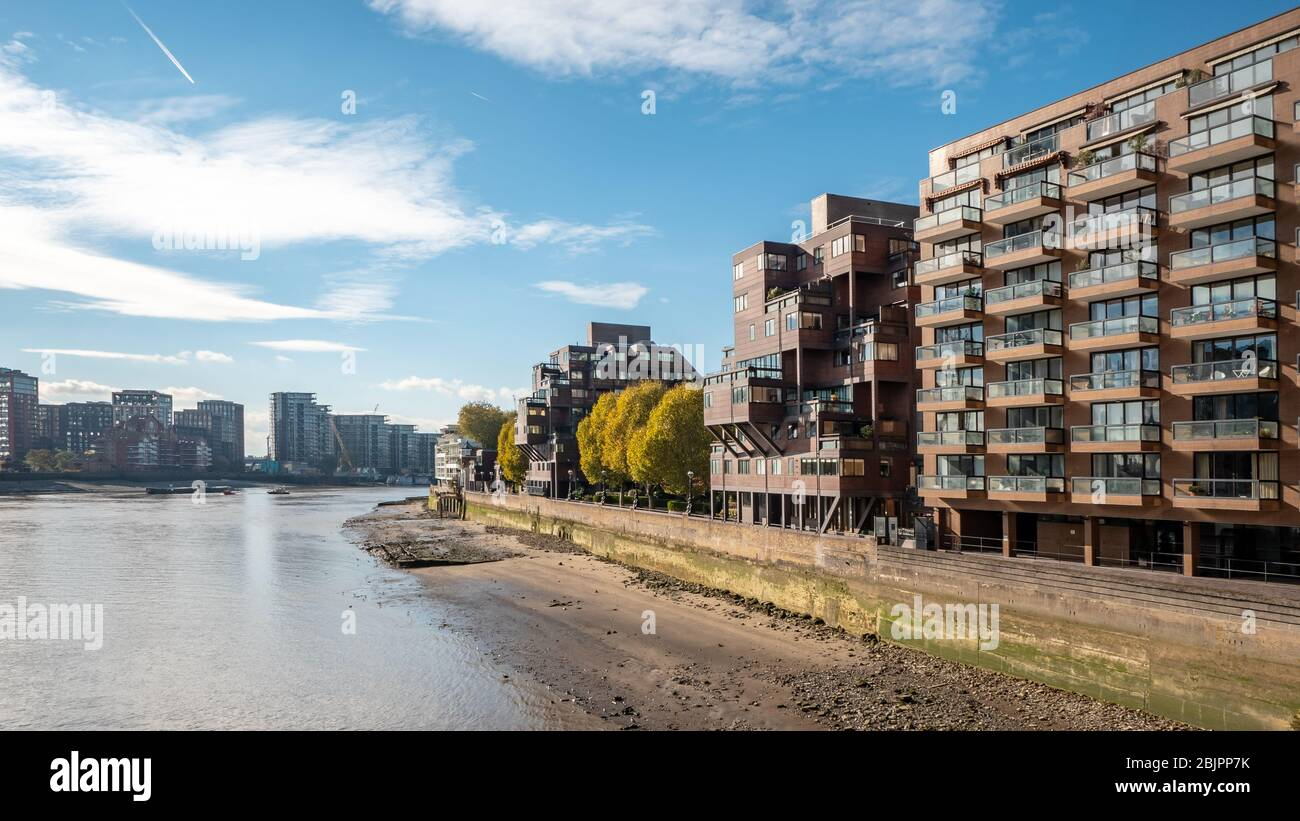 Modern residential architecture, River Thames, London. The riverside façade of contemporary flats on the Thames on a bright autumnal day. Stock Photo