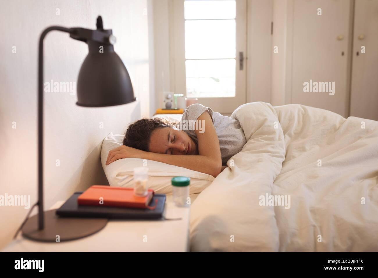 Sick Caucasian woman self isolating and social distancing in quarantine lockdown during coronavirus Stock Photo