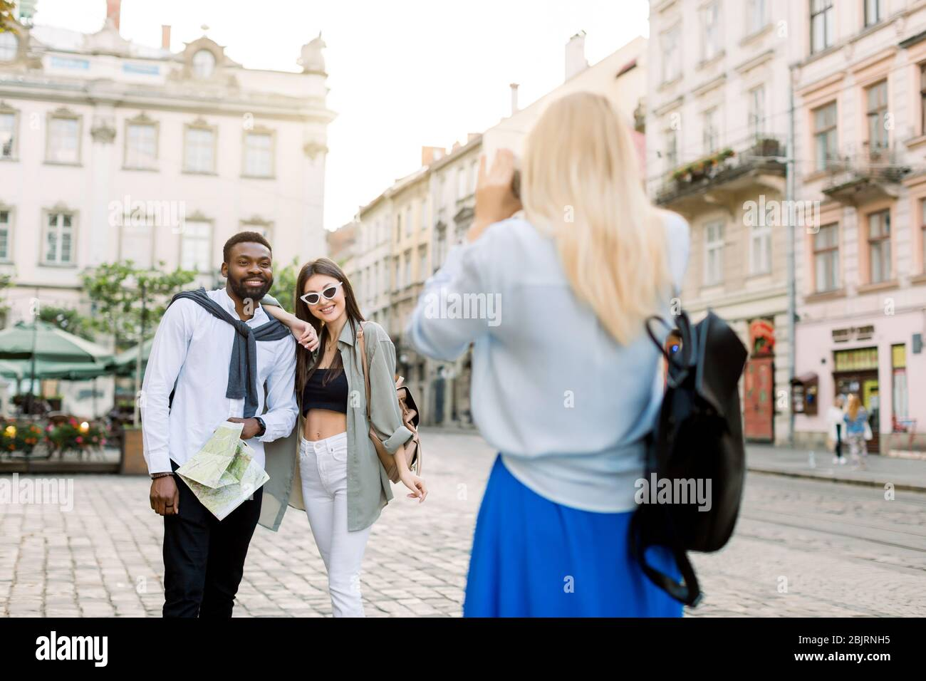 Excited cheerful mix raced couple, African man and Caucasian girl, enjoying walking outdoors, in the center of ancient European city, while their Stock Photo