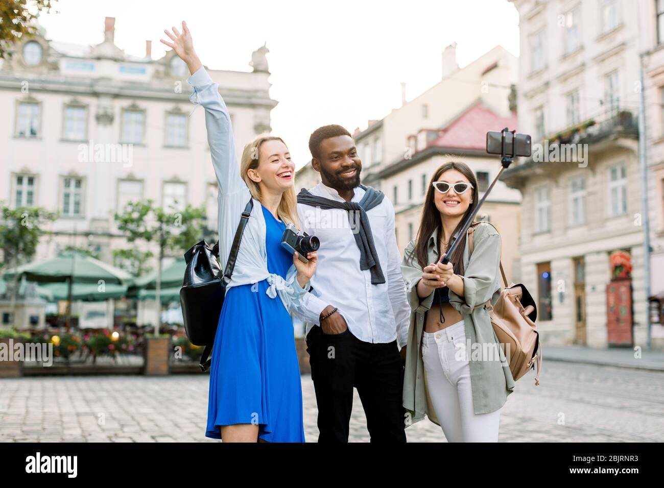 Excited cheerful mix raced friends enjoying walking outdoors in European city. Man and two women walking outside, hugging each other, laughing and Stock Photo