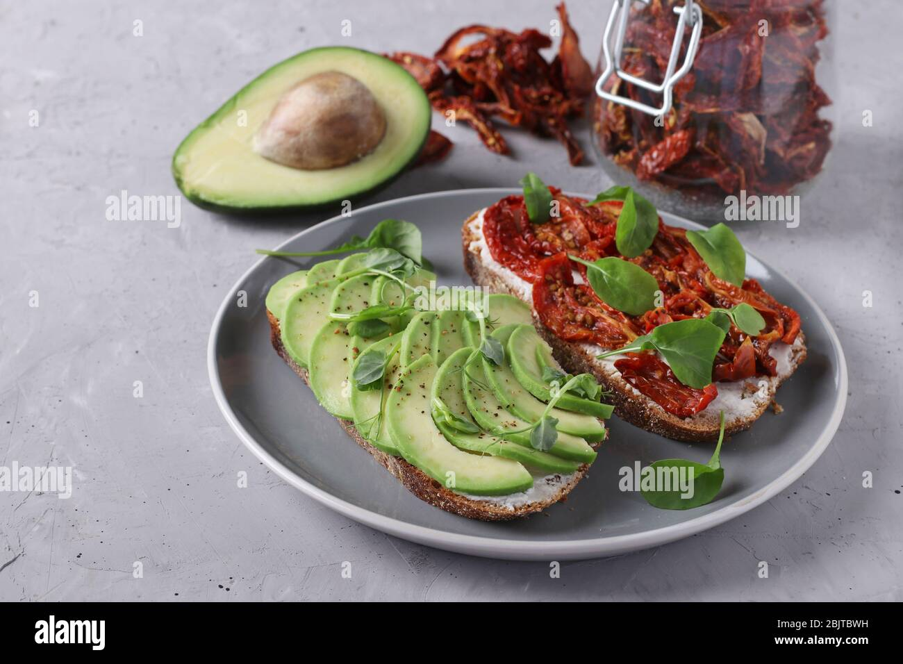 Two sandwiches with avocado, dried tomatoes, arugula and peas microgreen on gray plate on gray concrete background, Closeup, Space for text Stock Photo