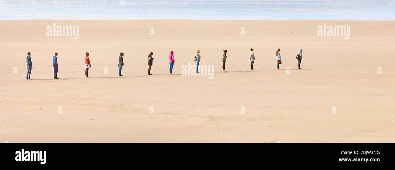 Young people queueing two meteres apart to maintain social distancing on a beach during the Coronavirus pandemic of 2020 - UK Stock Photo