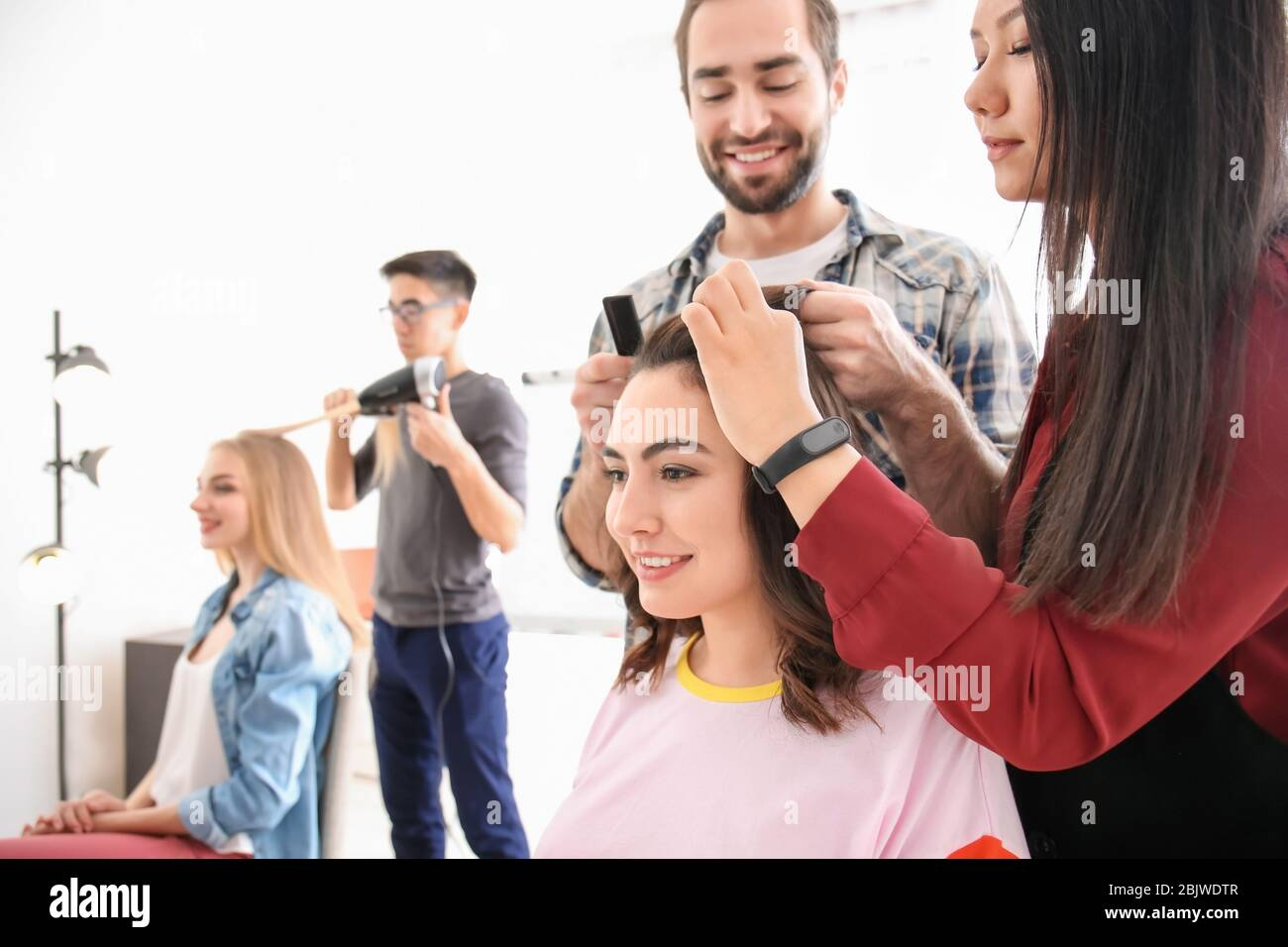 Professional hairdresser and trainees working with clients in
