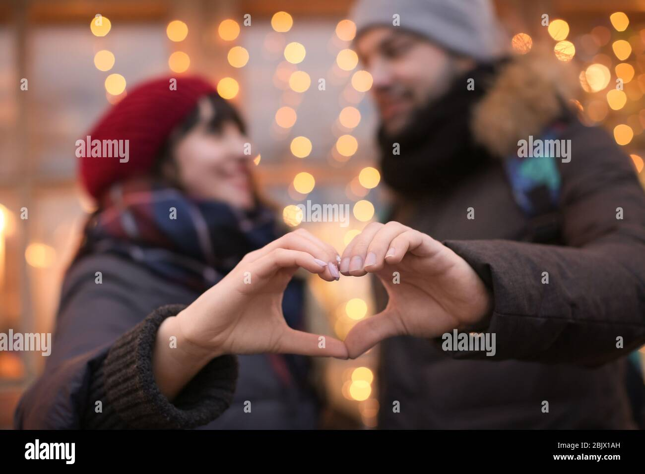 Young Loving Couple Making Heart With Hands Outdoors On Winter Day