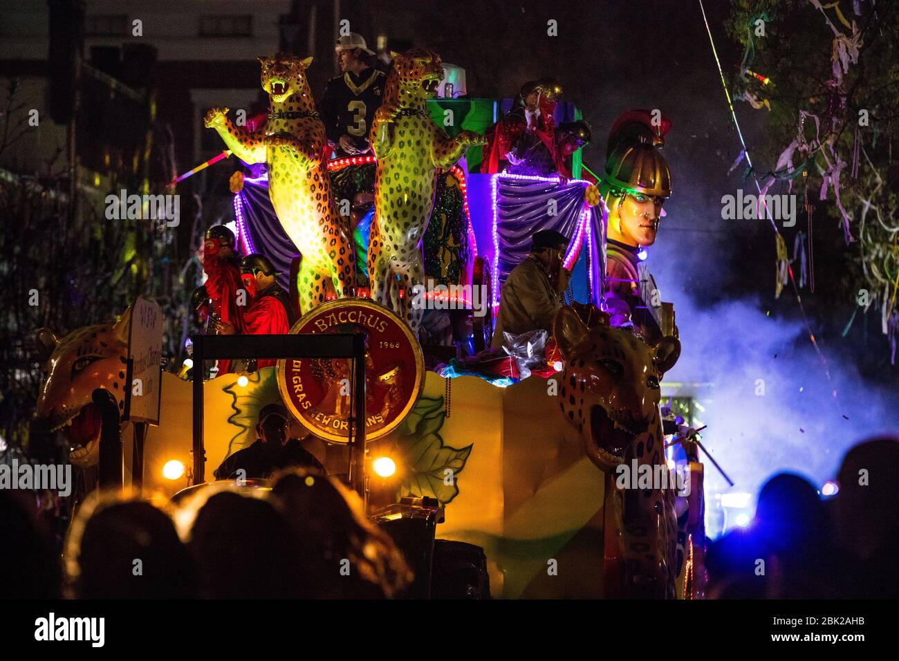 A float from Krewe Bacchus tossing beads to spectators during Mardis Gras in New Orleans, Louisiana Stock Photo