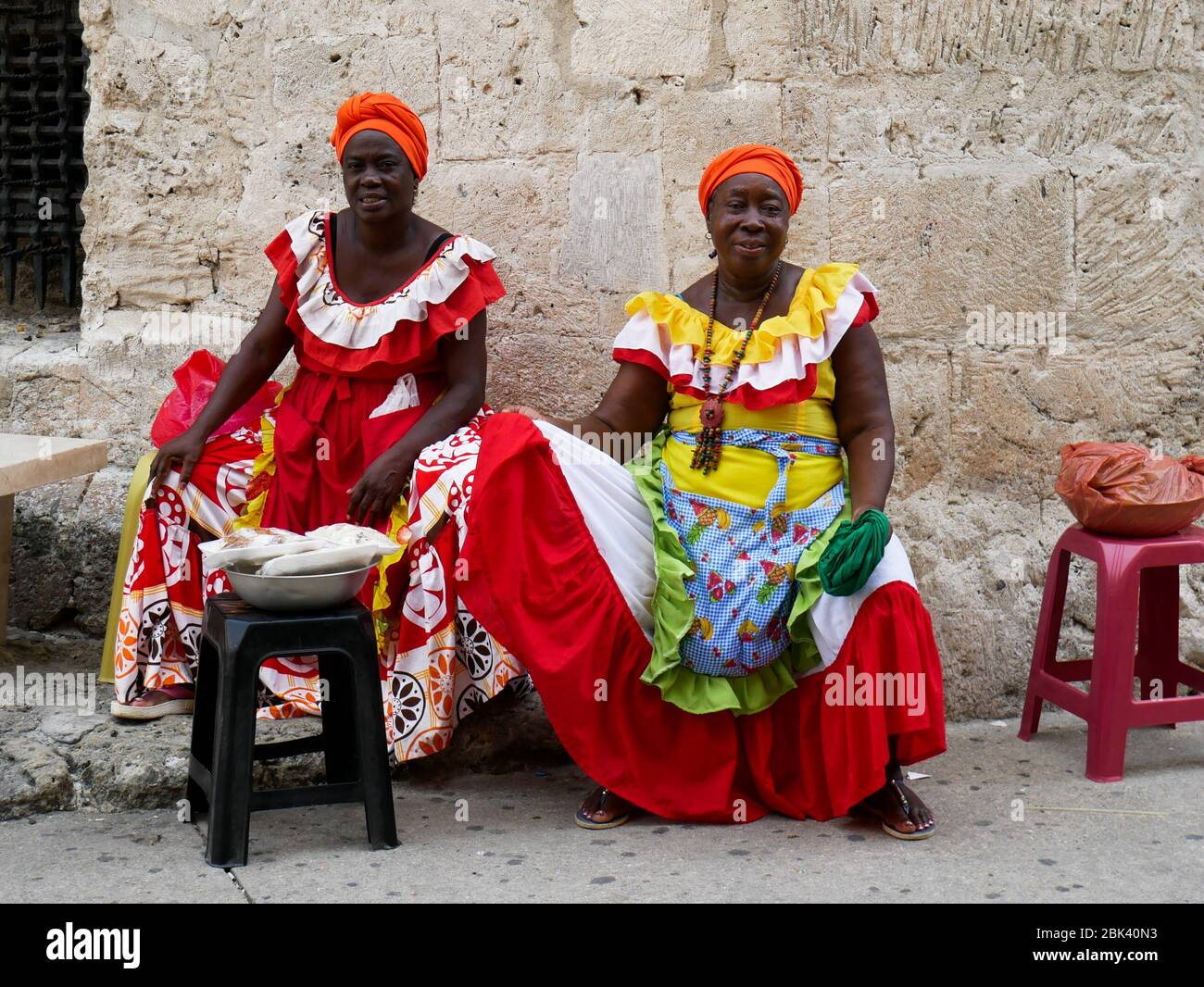 Cartagena, Colombia, August 1 2019: two tipical fruit street sellers palenqueras with colorful dresses seated resting from the front Stock Photo