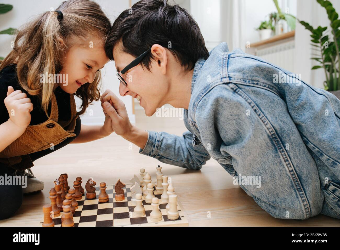 Friendly competition concept. dad and dau playing chess and batting heads Stock Photo