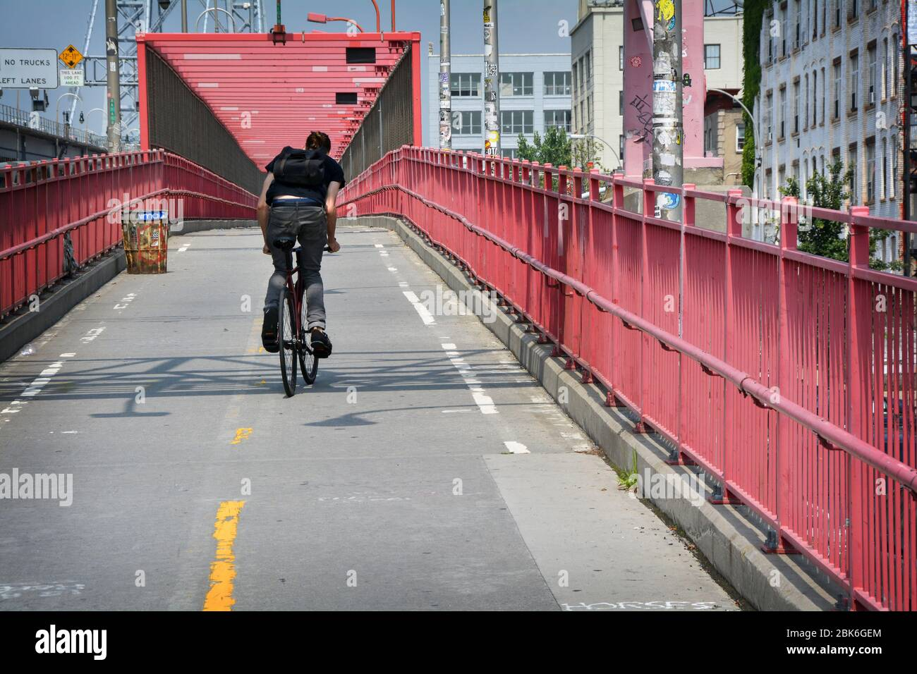 An unidentified young man cycling over the Williamsburg Bridge bike & running path from Brooklyn, to Manhattan. - Stock Photo