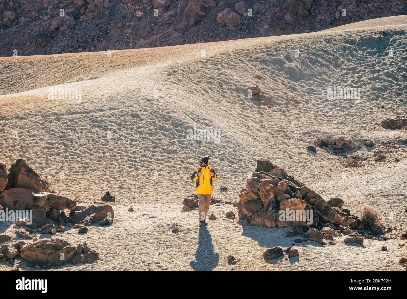 Wild hiking outdoor activity in the mountain and desert scenic landscape - caucasian professional adventurer man walk and discover beautiful places - Stock Photo