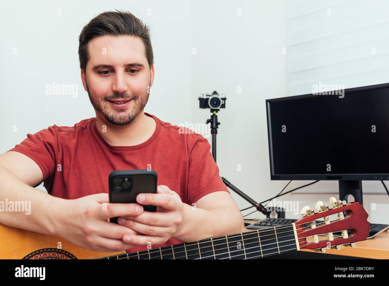 Blogger checking his phone before giving the guitar lesson from his home recording studio. Learning online concept. Stock Photo