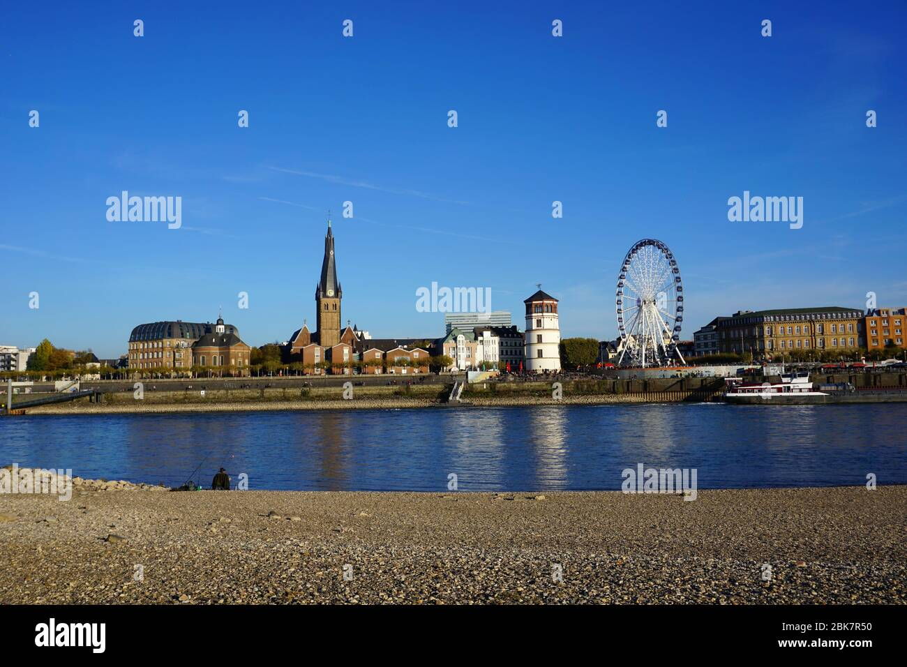 Panoramic view across Rhine river from the Düsseldorf district of Oberkassel, with white castle tower and Ferris wheel. Late afternoon sun, blue sky. Stock Photo