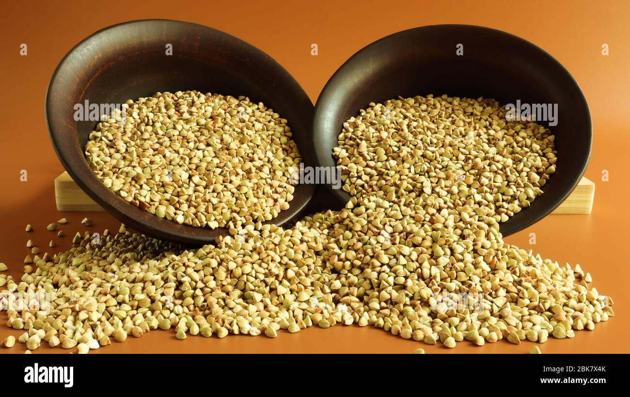 Buckwheat scattered background, raw green buckwheat in a brown clay bowl or plate. Healthy groats. Organic raw non-fried vegetarian food. The concept Stock Photo