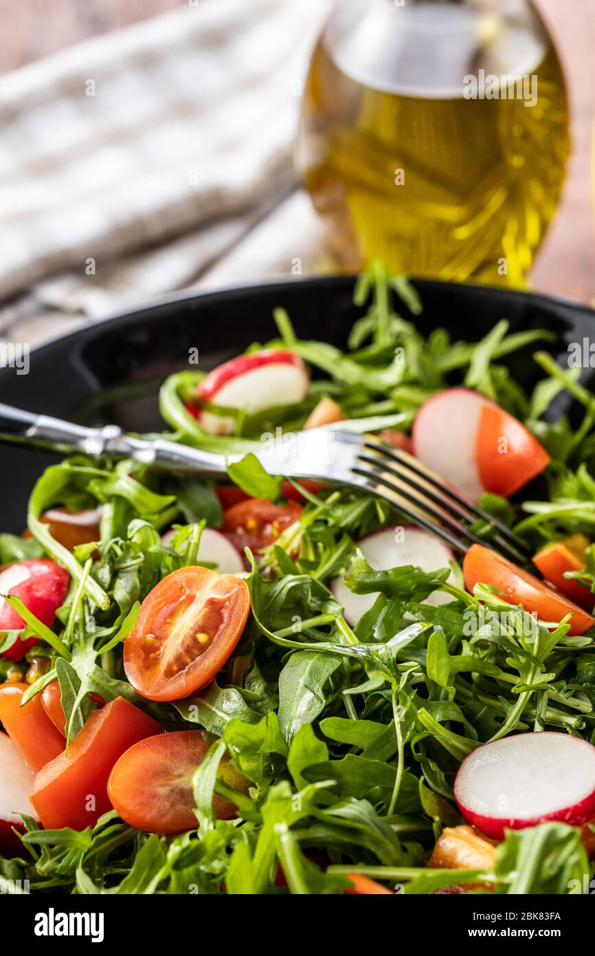 Fresh arugula salad with radishes, tomatoes and red peppers on plate. Stock Photo