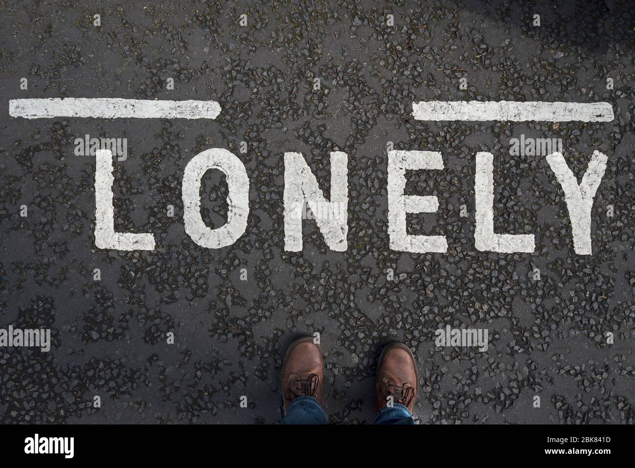 """Road marking with the word """"Lonely"""" and the male photographer's feet. Concept loneliness. Stock Photo"""