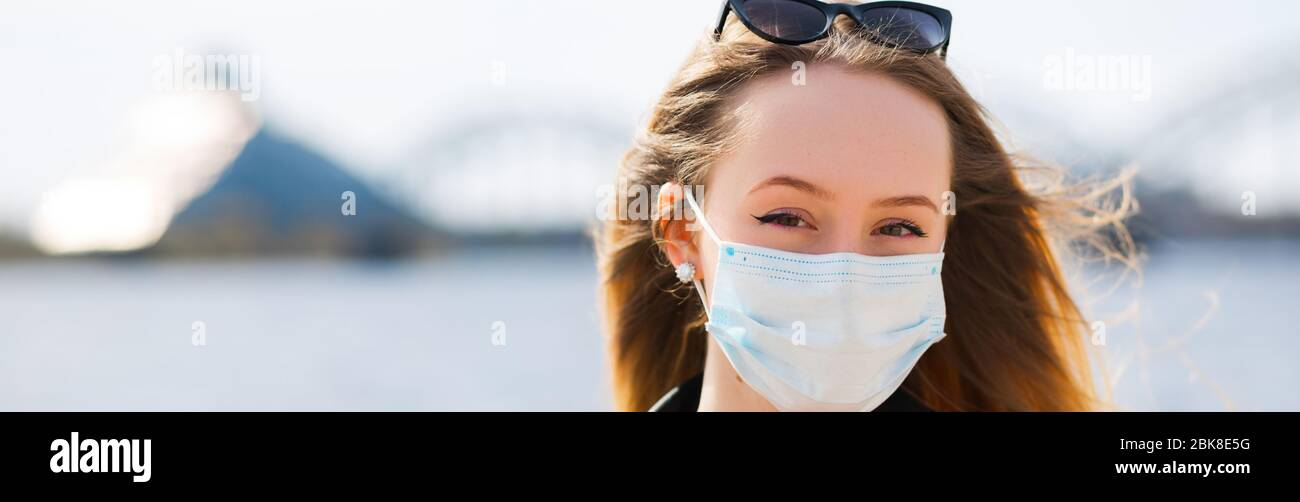 Young blonde woman in surgical mask and glasses on top banner Stock Photo