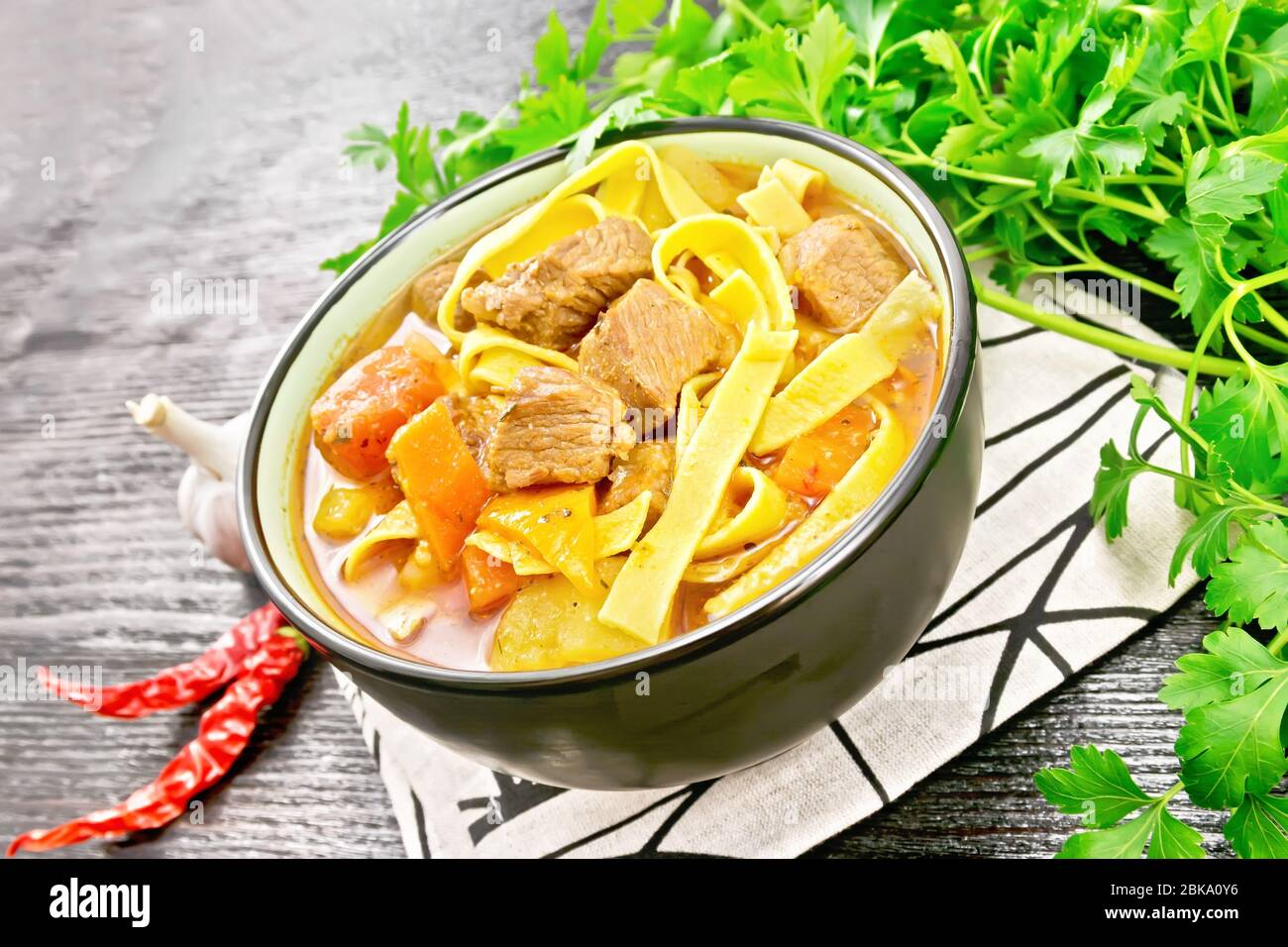 Central Asian national dish Lagman of meat, noodles and vegetables in bowl on a napkin, garlic, parsley on black wooden board Stock Photo