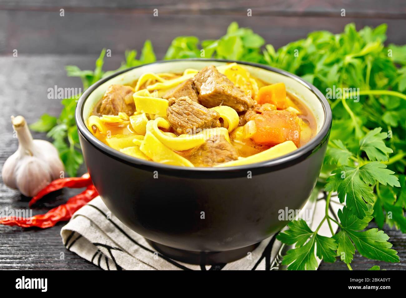 Central Asian national dish Lagman of meat, noodles and vegetables in bowl on a towel, garlic, parsley on wooden board background Stock Photo