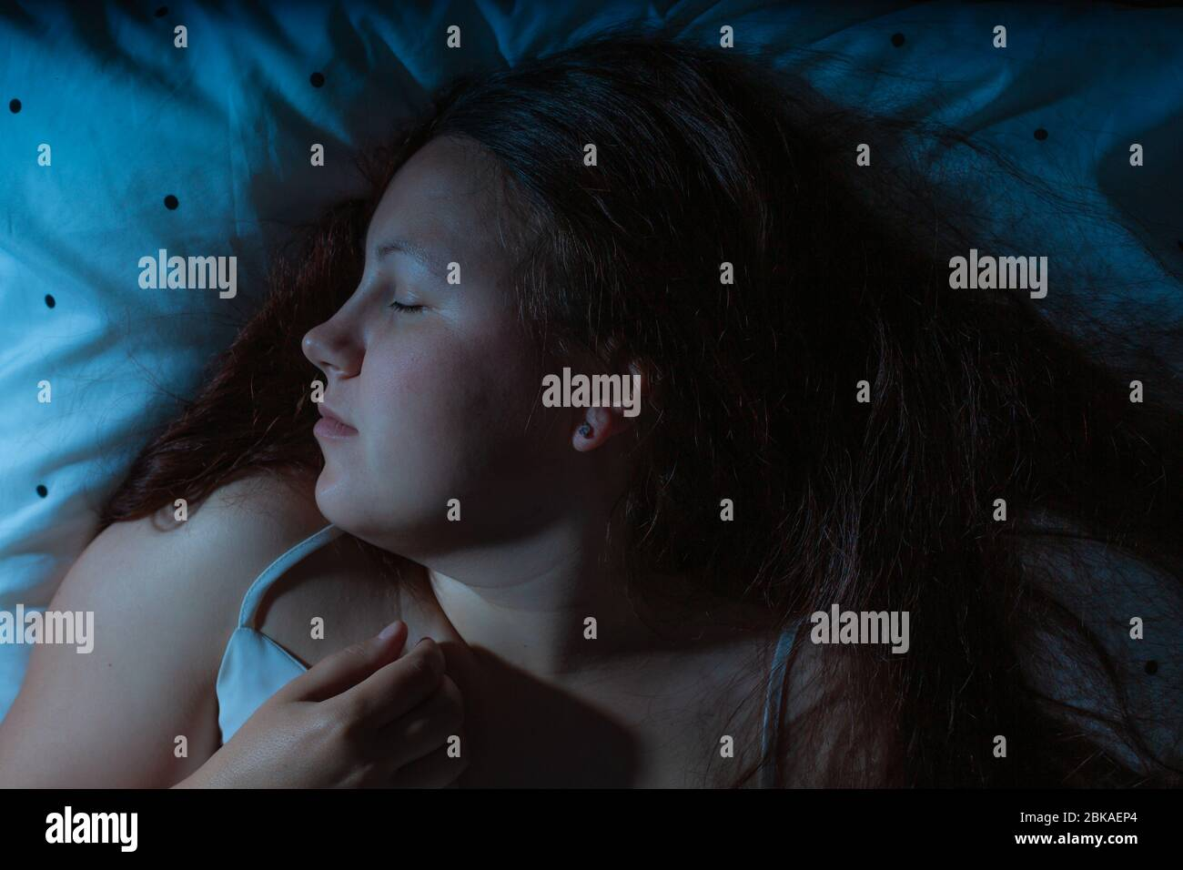 Top view of young woman sleeping cozily on a bed at night, blue nightly colours Stock Photo