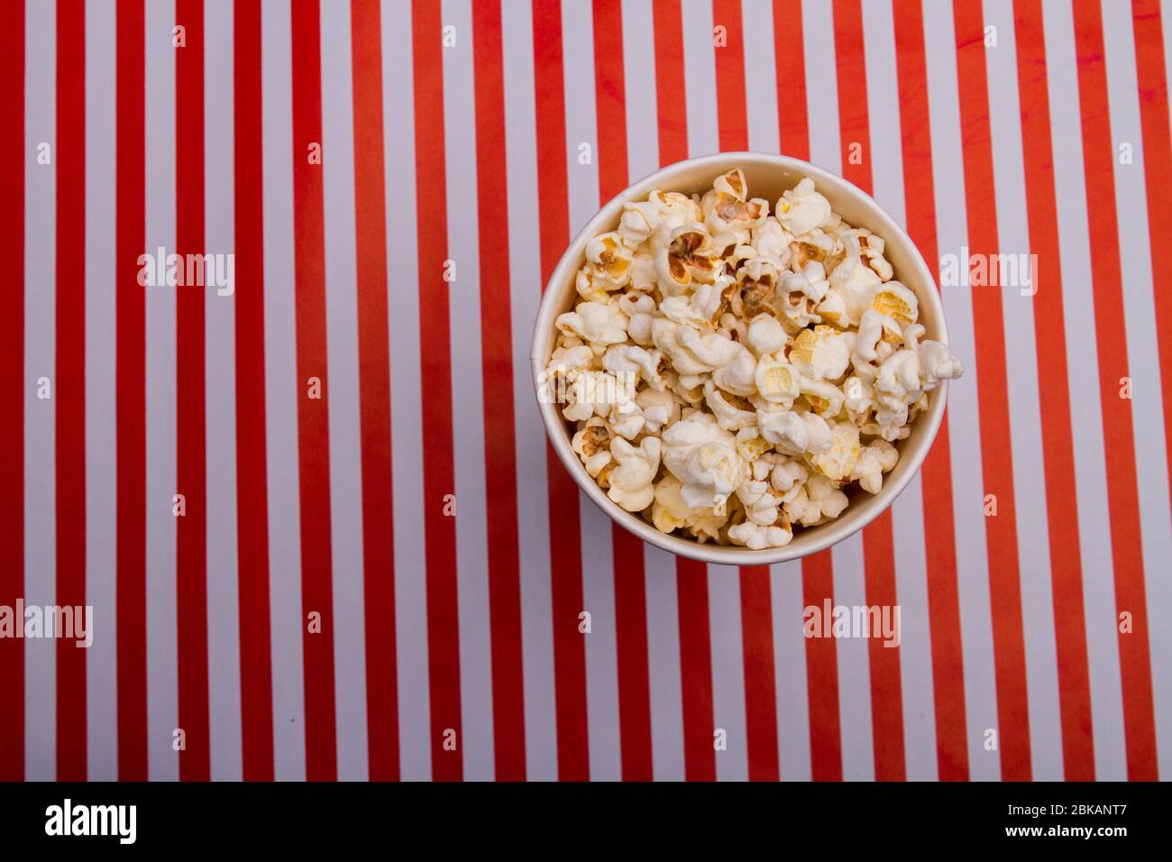 Top view of popcorn in bowl on striped background Stock Photo