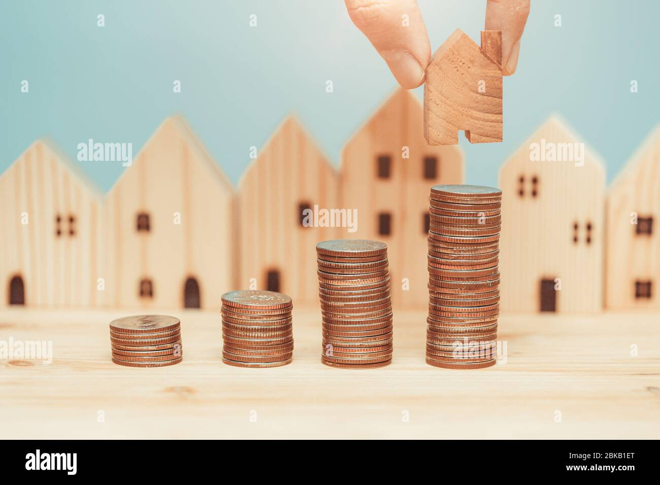 Coin stack with wooden home model for saving money to buy a new home concept. Stock Photo