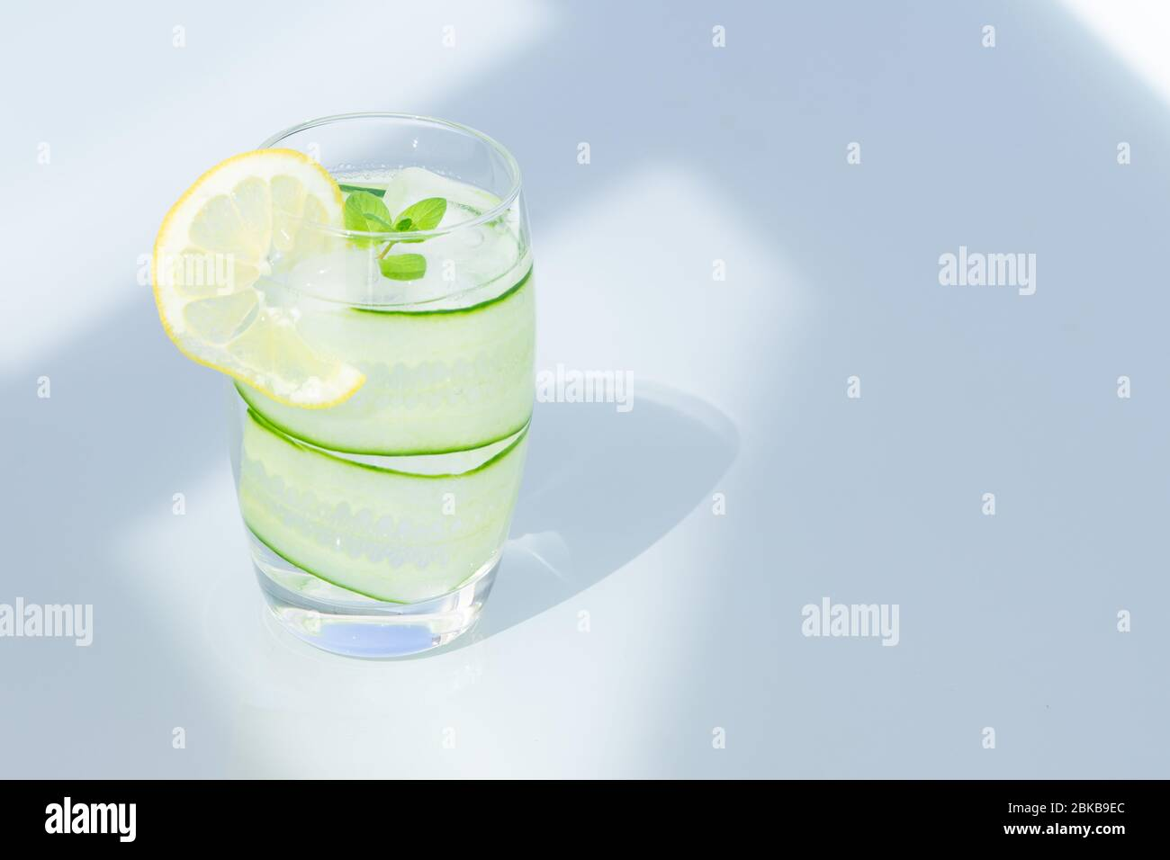 Glass of water with lemon, ice, and cucumber isolated. copy space.  Stock Photo