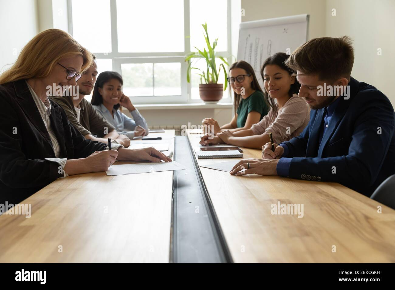 Smiling adult businesswoman signing up documents with serious businessman. Stock Photo