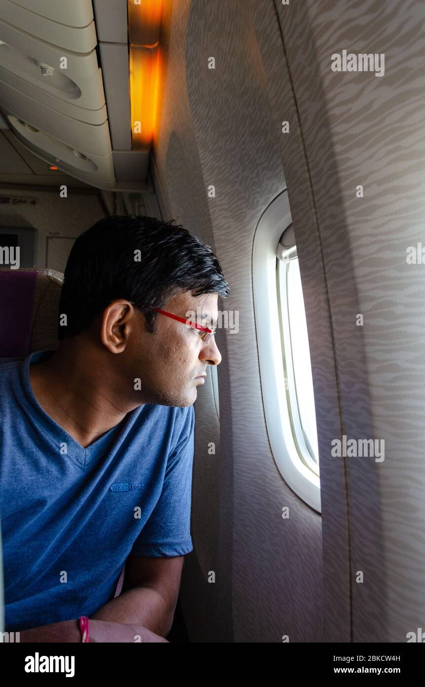Close-up portrait of an adult man looking out of an airplane window with a tense look on face. Stock Photo