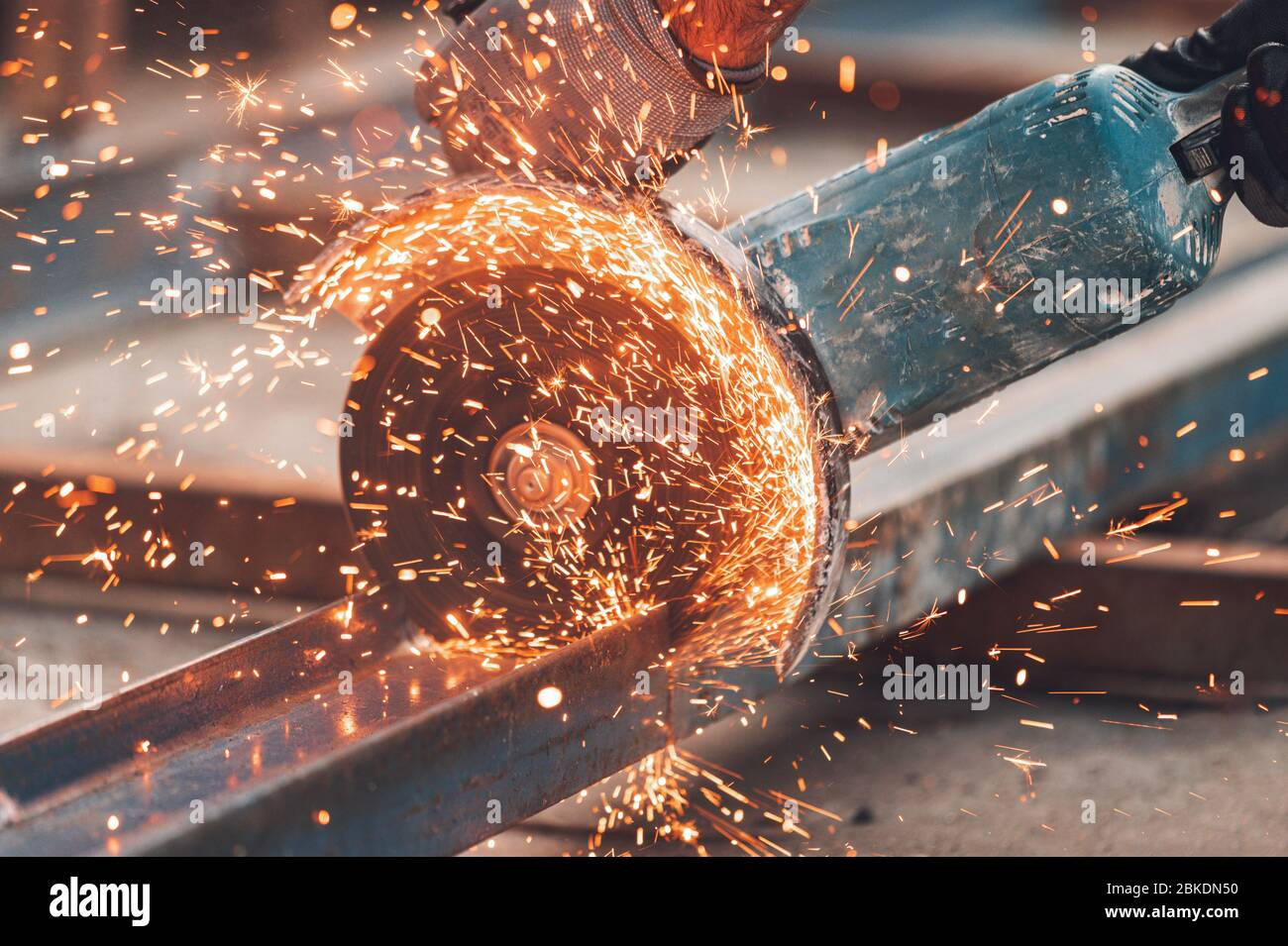 Construction worker using Angle Grinder cutting Metal at construction site . Stock Photo