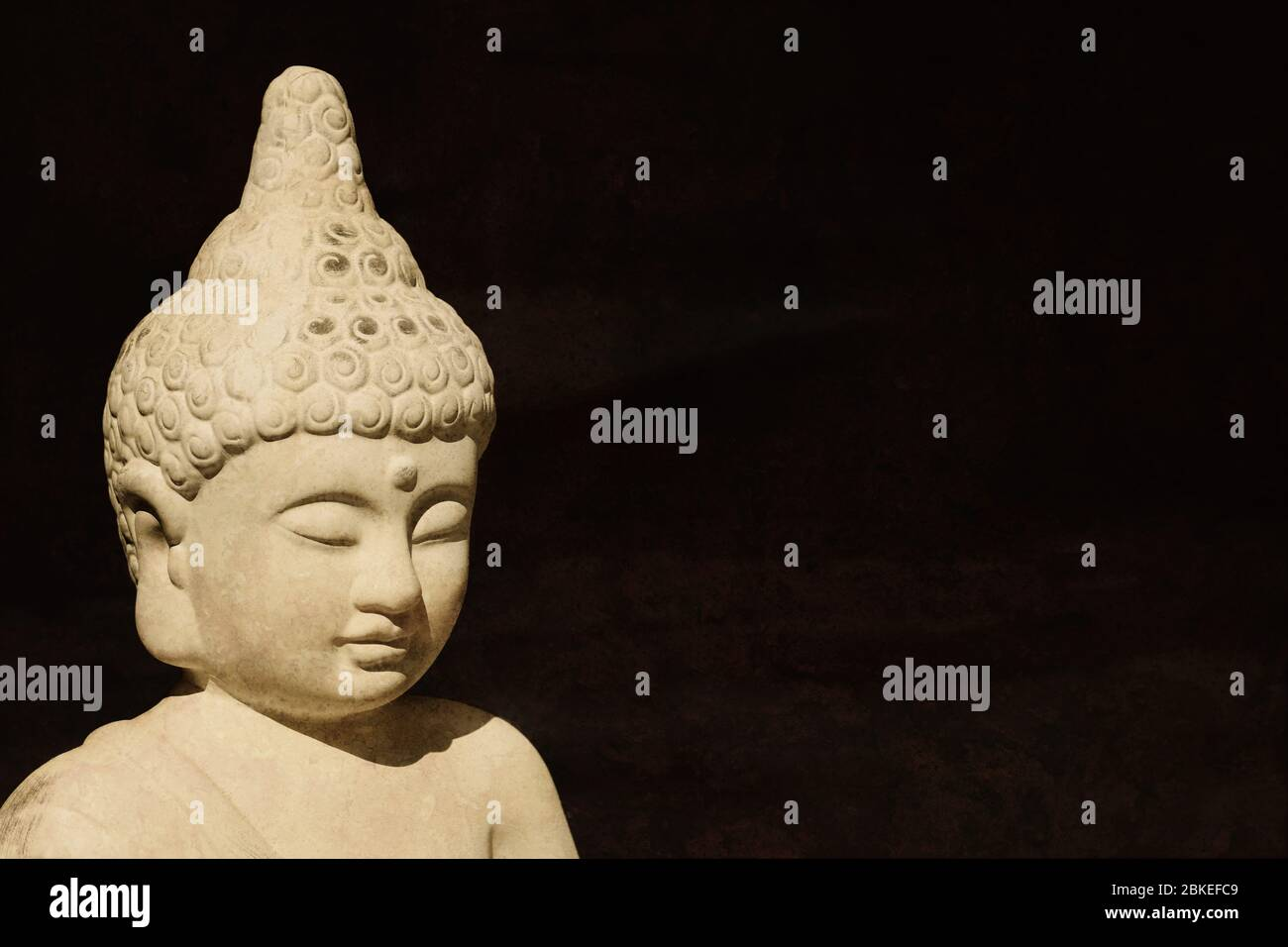 buddha statue head made of stone - buddhism meditation enlightenment religion faith and spirituality concept - black background with copy space Stock Photo