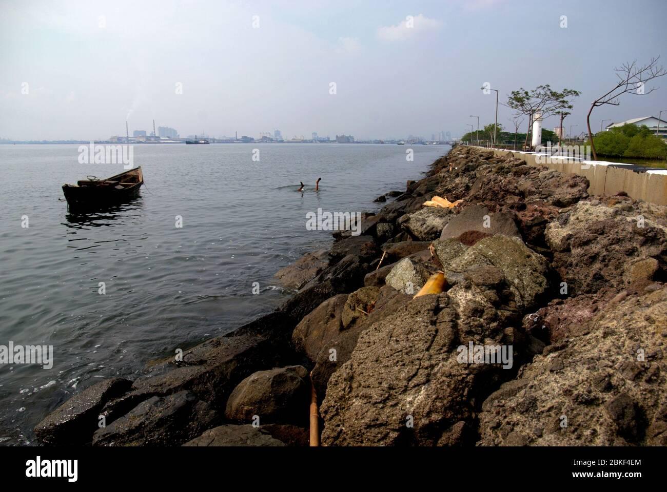 Man duckdiving to search usable items on the coastal waters of Jakarta in Muara Baru area. Archival photo. North Jakarta, Special Capital Region of Jakarta, Indonesia. Photo: Reynold Sumayku Stock Photo