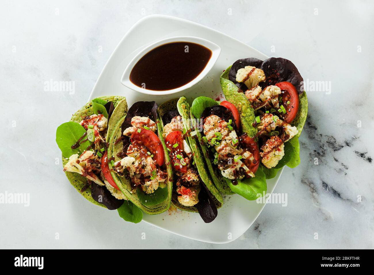 gluten-free vegan green tachos made from chickpea flour with spinach and toppings from baked cauliflower and lettuce with sweet and sour sauce based o Stock Photo