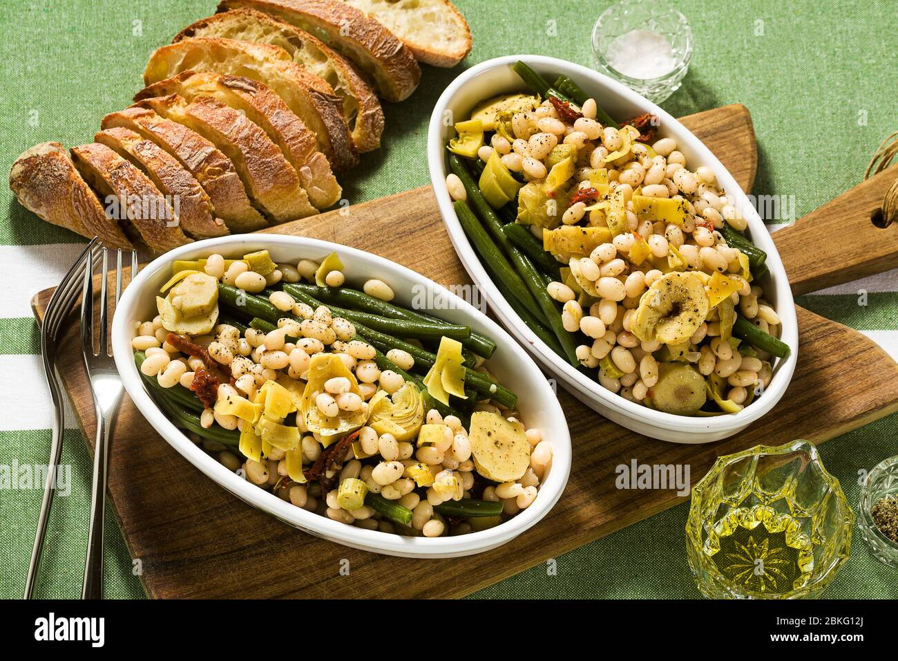Cannellini nutritious white bean salad with green beans, sun-dried tomatoes and artichokes in oil. Traditional italian food Stock Photo