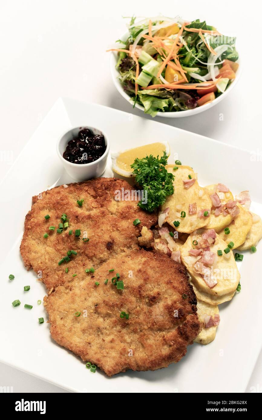 german breaded organic pork schnitzel with bacon fried potatoes cranberry sauce and salad on white studio background Stock Photo