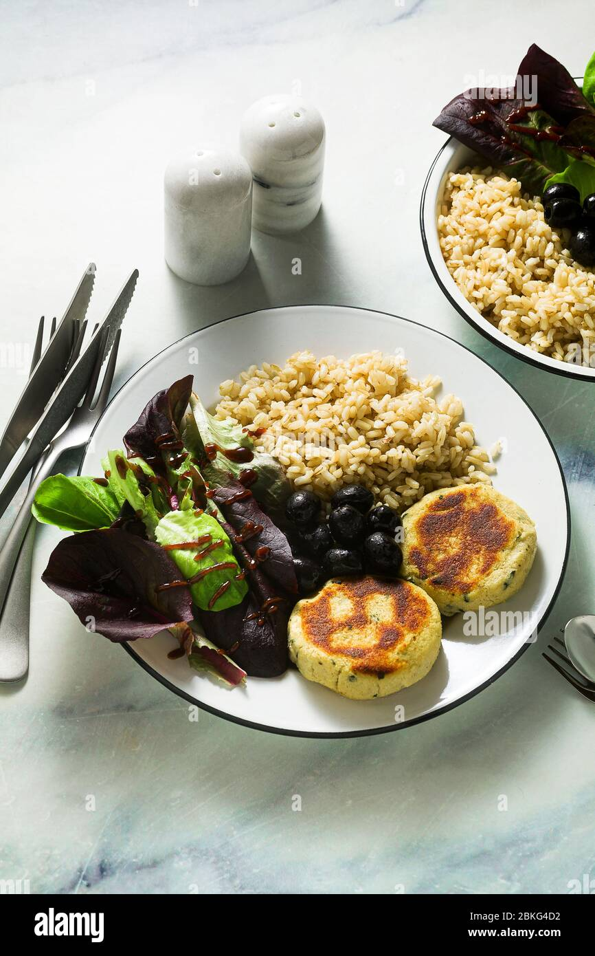 A simple vegan lunch or dinner for a family of two adults and a child. brown rice with soy okara and potato patties with fresh salad and olives on a m Stock Photo