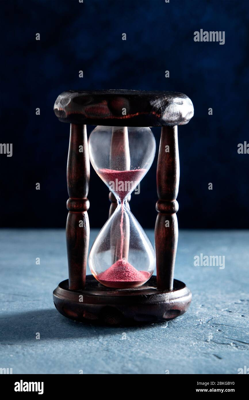 Time concept. An hourglass with flowing sand, time flies Stock Photo