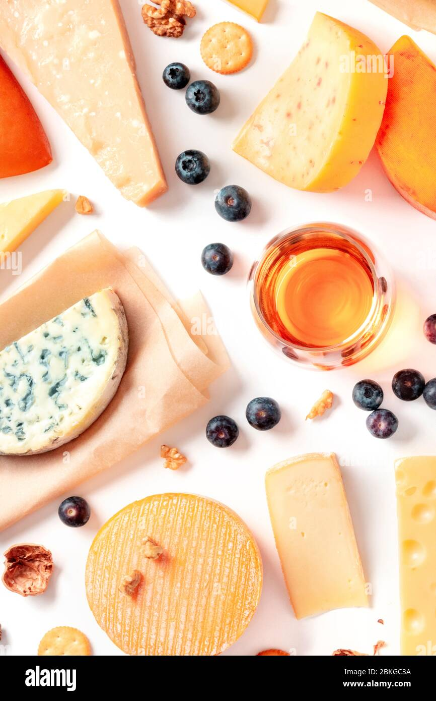 Cheese and wine tasting and pairing flat lay on a white background. Many different cheeses, overhead shot Stock Photo
