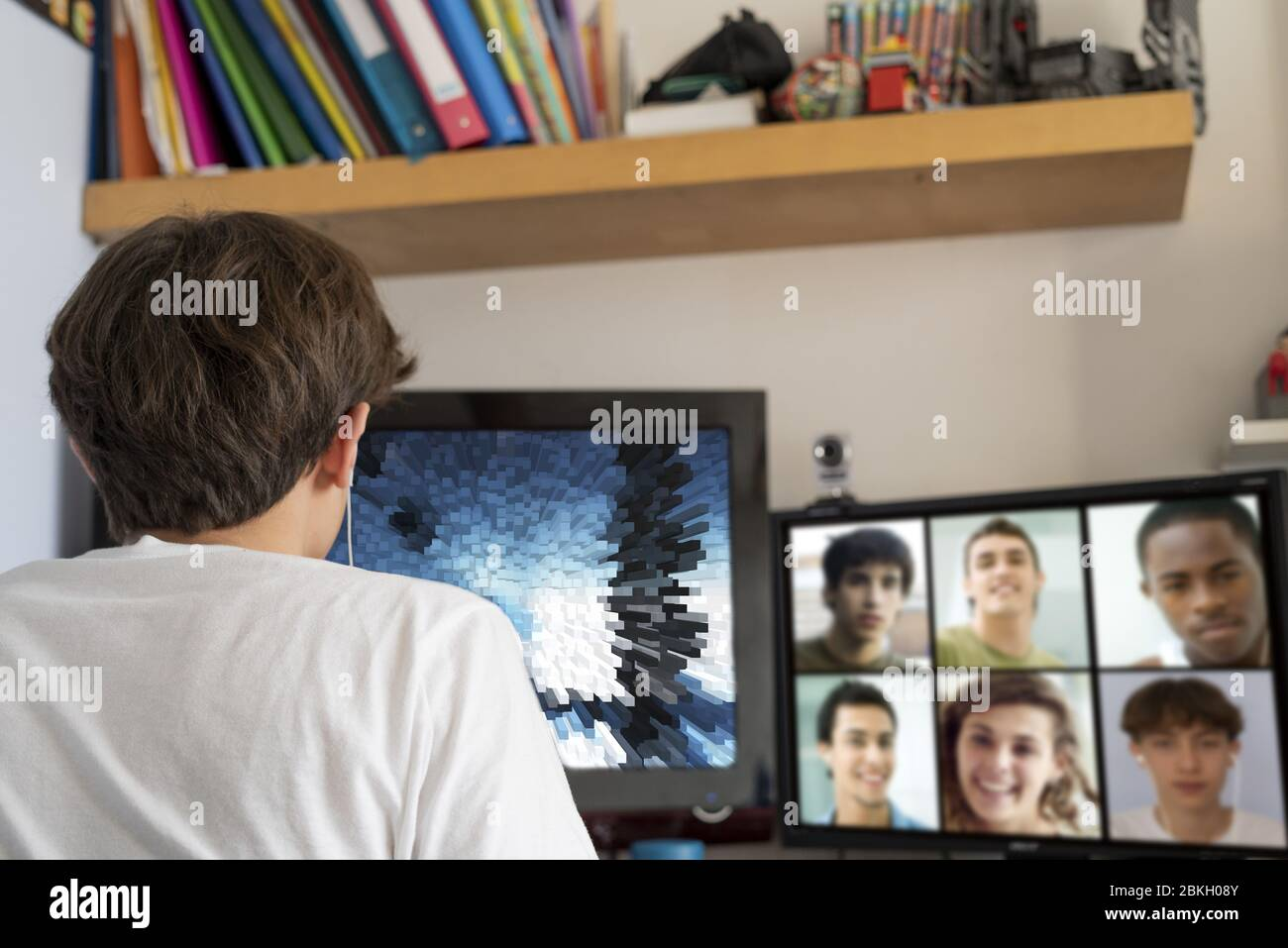 Teenage boy video chatting on the computer with friends at home Stock Photo