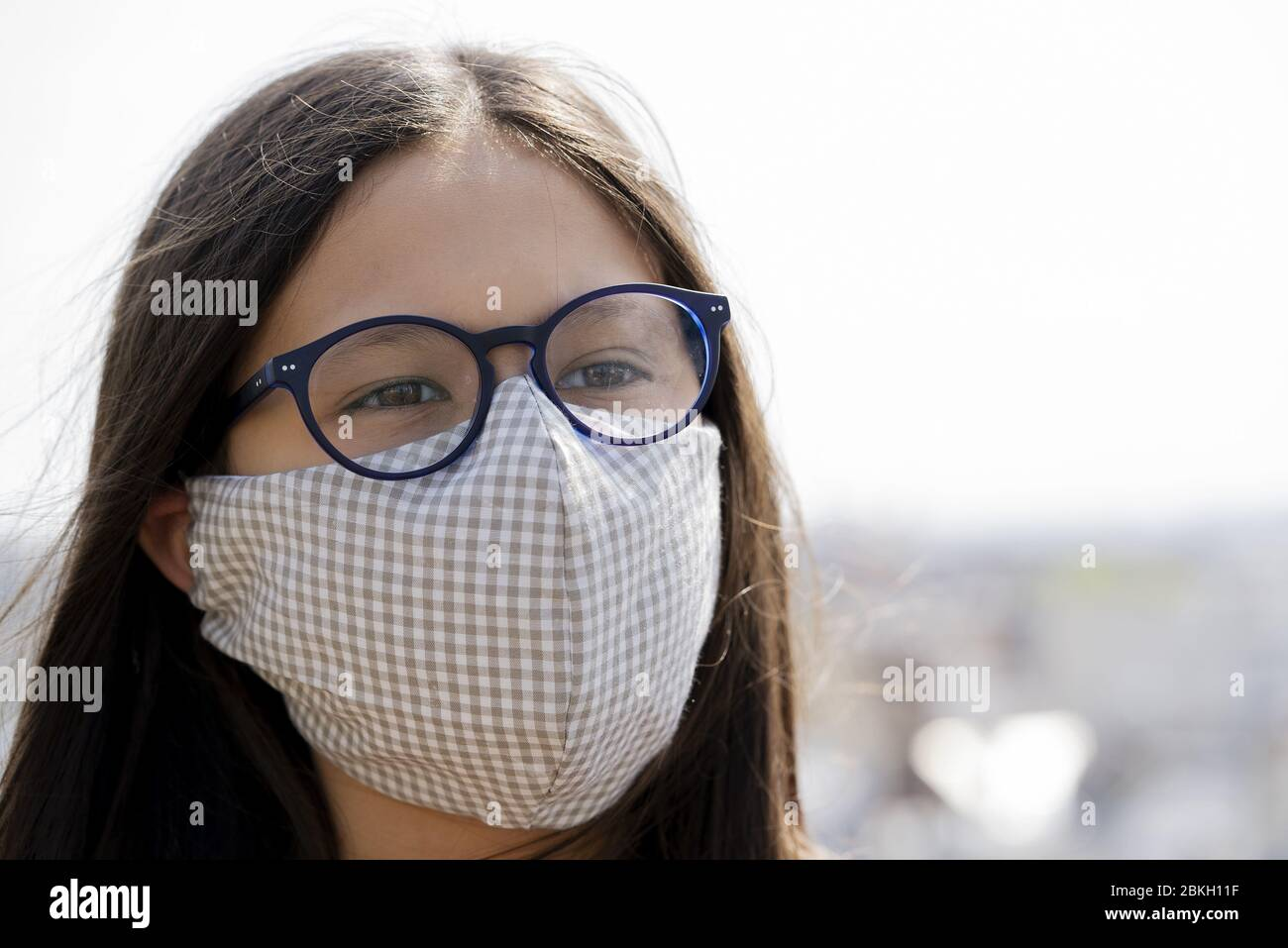 Close up of teenage girl wearing homemade face mask outdoors Stock Photo