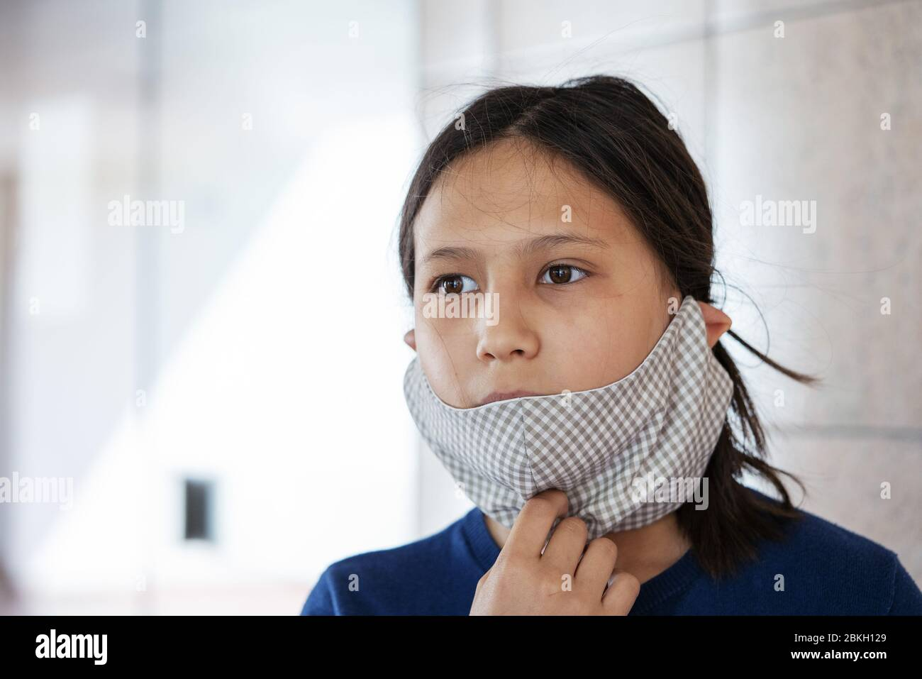 Close up of teenage girl wearing homemade face mask indoors Stock Photo