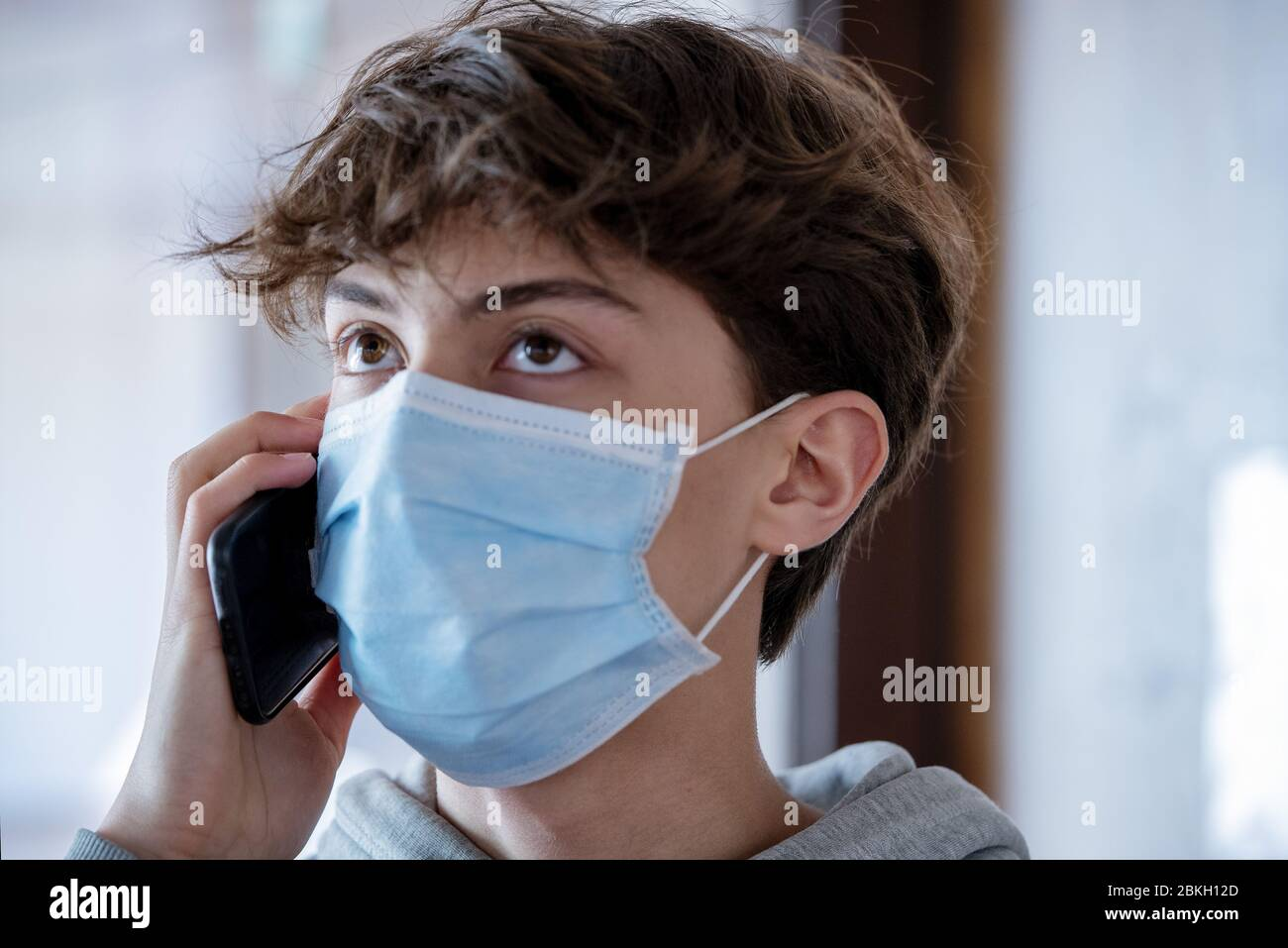 Close up of teenage boy with medical mask talking on smartphone during lockdown Stock Photo