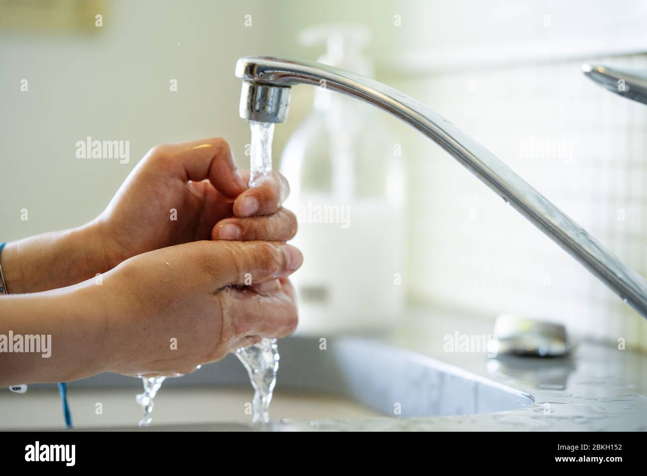 Woman washing hands with water in bathroom sink Stock Photo