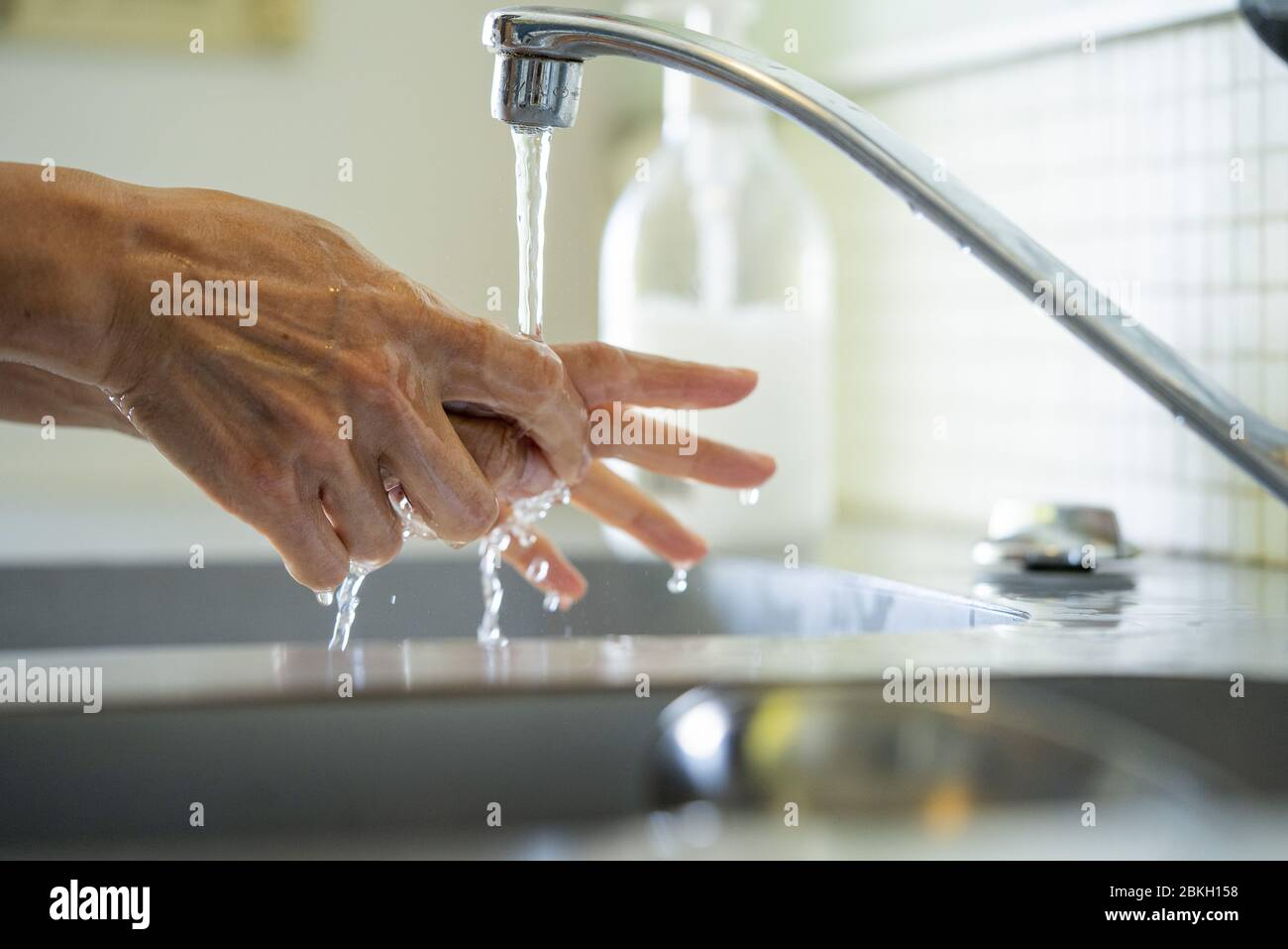 Man washing hands with water in bathroom sink Stock Photo