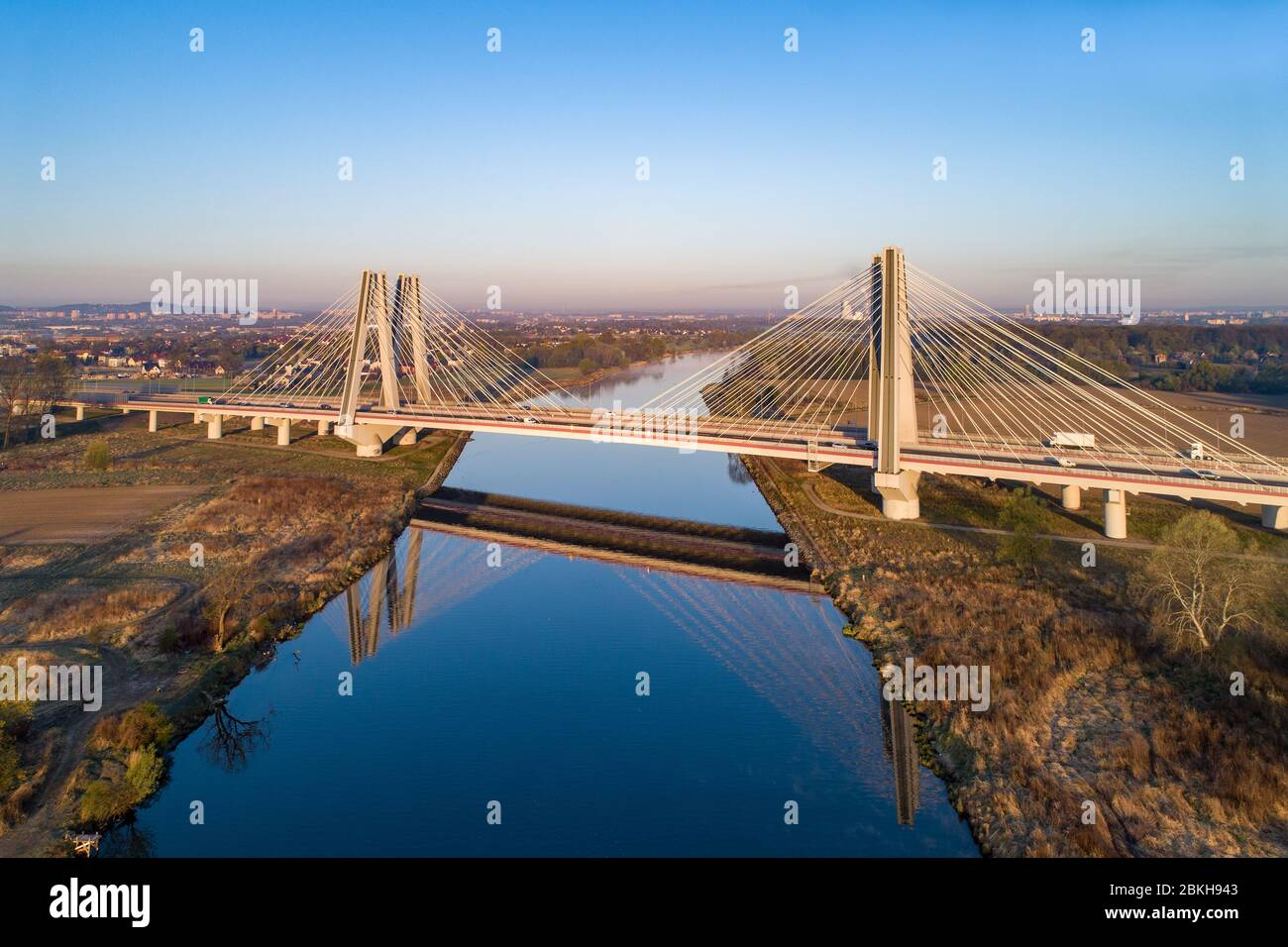 New modern double cable-stayed bridge with wide three-lane roads over Vistula River in Krakow, Poland, and its reflection in water at sunrise. Stock Photo