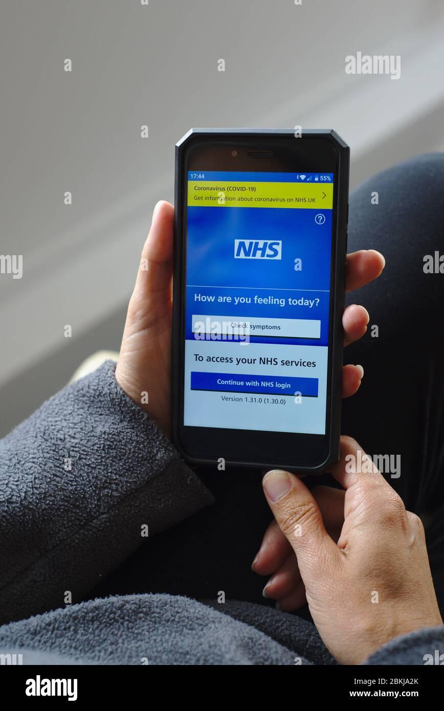 NHS app on smartphone coronavirus COVID-19 link and symptoms check. Stock Photo