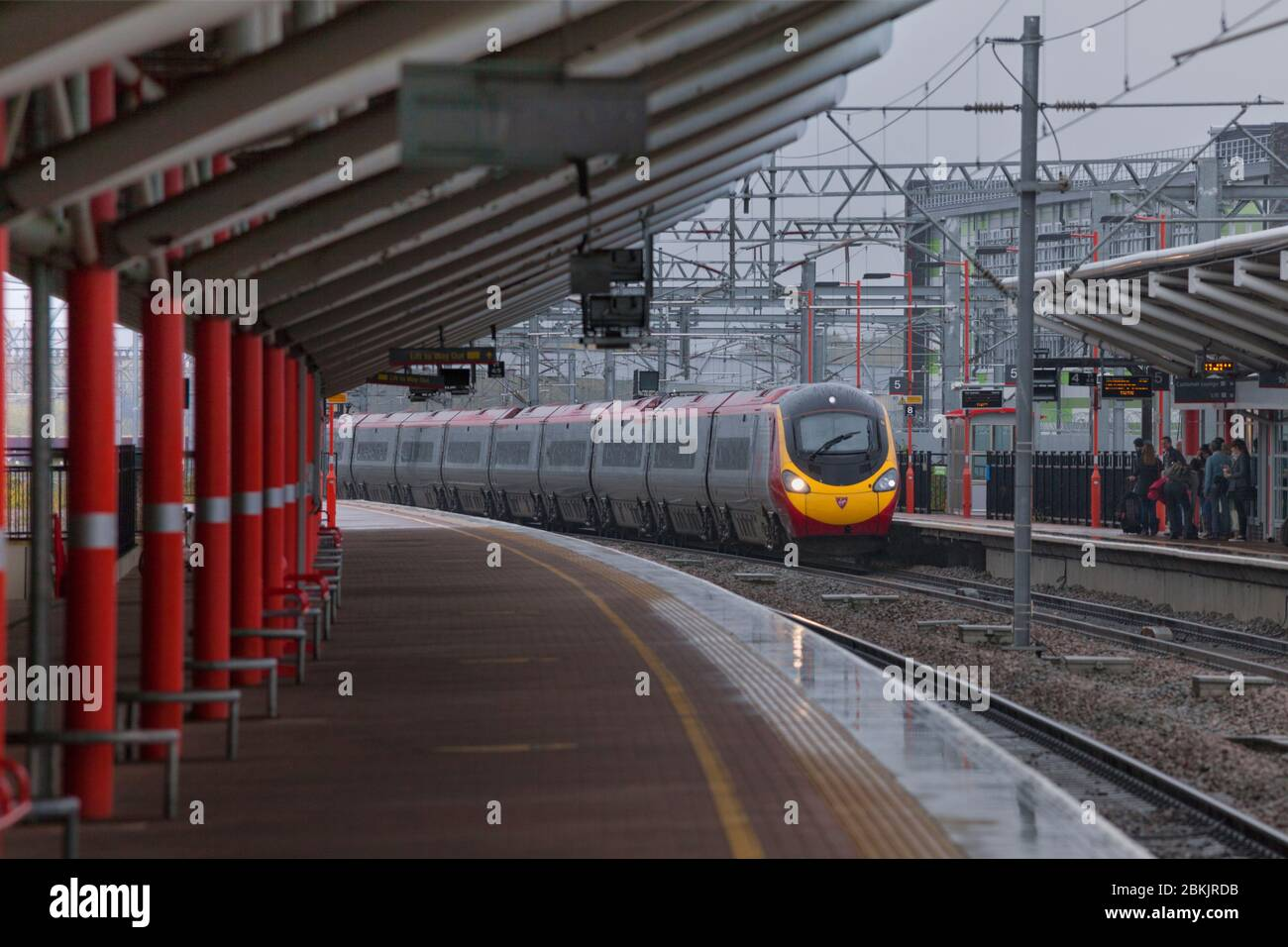 Virgin Trains Alstom class 390 Pendolino train passing Rugby railway station in the rain with the station canopy. Stock Photo