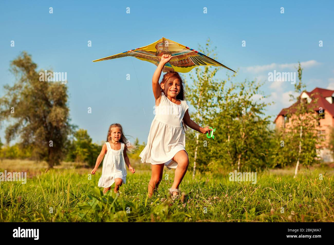 Happy little girls with kite running on meadow in spring park. Children having fun playing outdoors Stock Photo