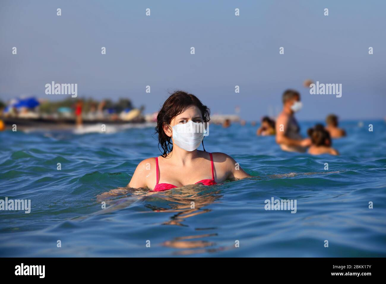 Young caucasian woman basking in the sea in a protective face mask. A beautiful female uses personal protective equipment during the Covid-19 pandemic Stock Photo
