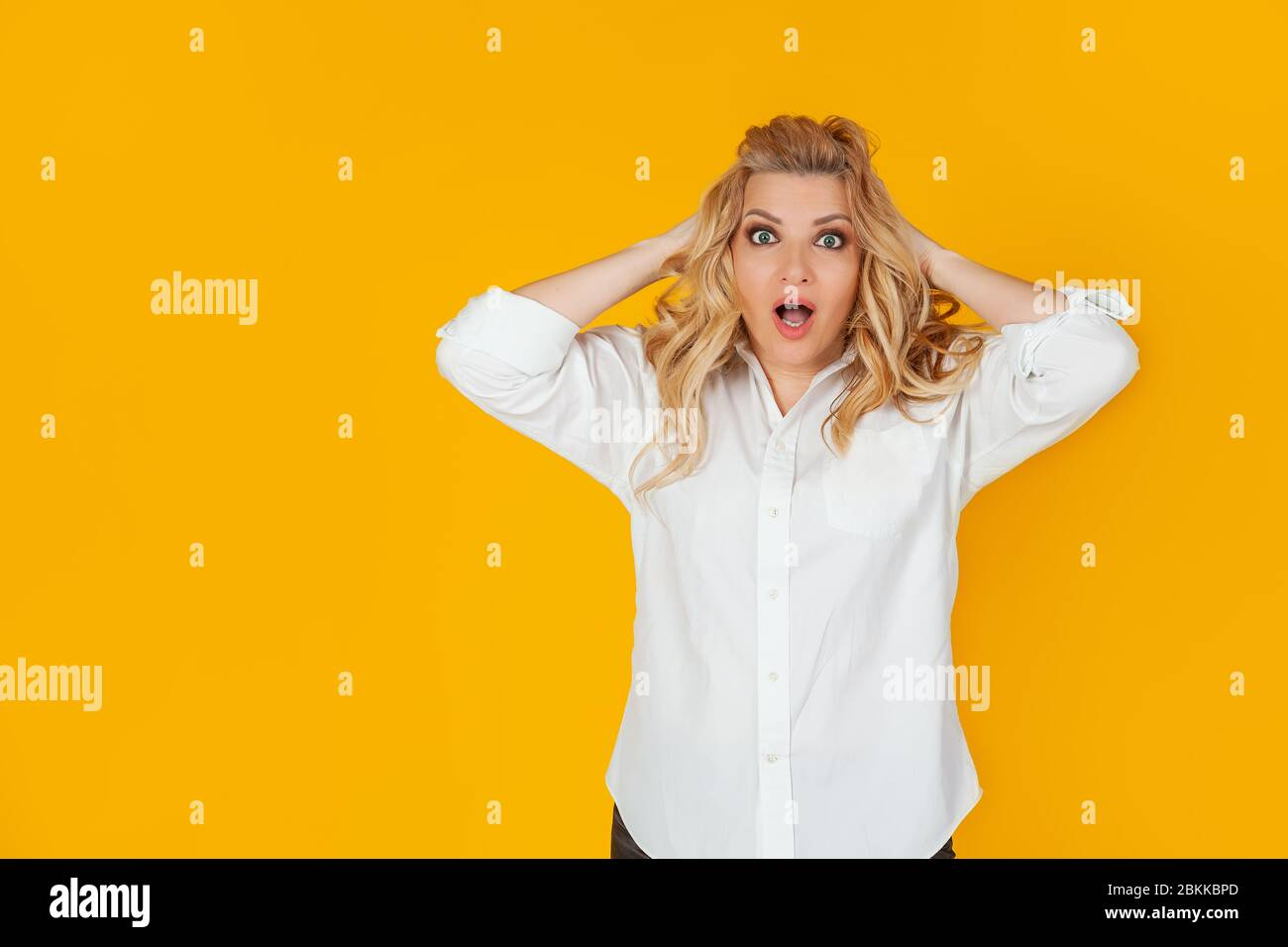 Portrait of a woman in a panic with her hands clutching her head, excited and looking panicky down, hands clutching her head, breaking an expensive thing, alarmed indecisive, on a yellow background Stock Photo