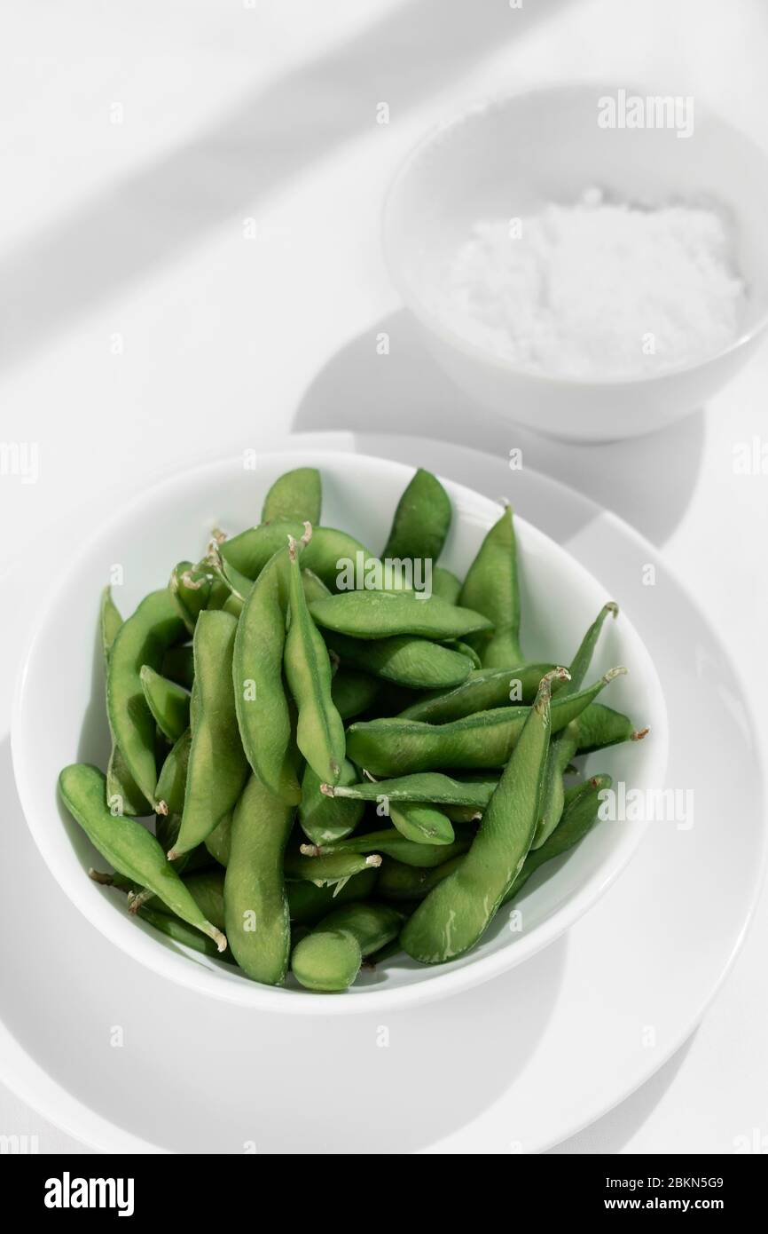 organic edamame beans snack in bowl on table with sea salt Stock Photo