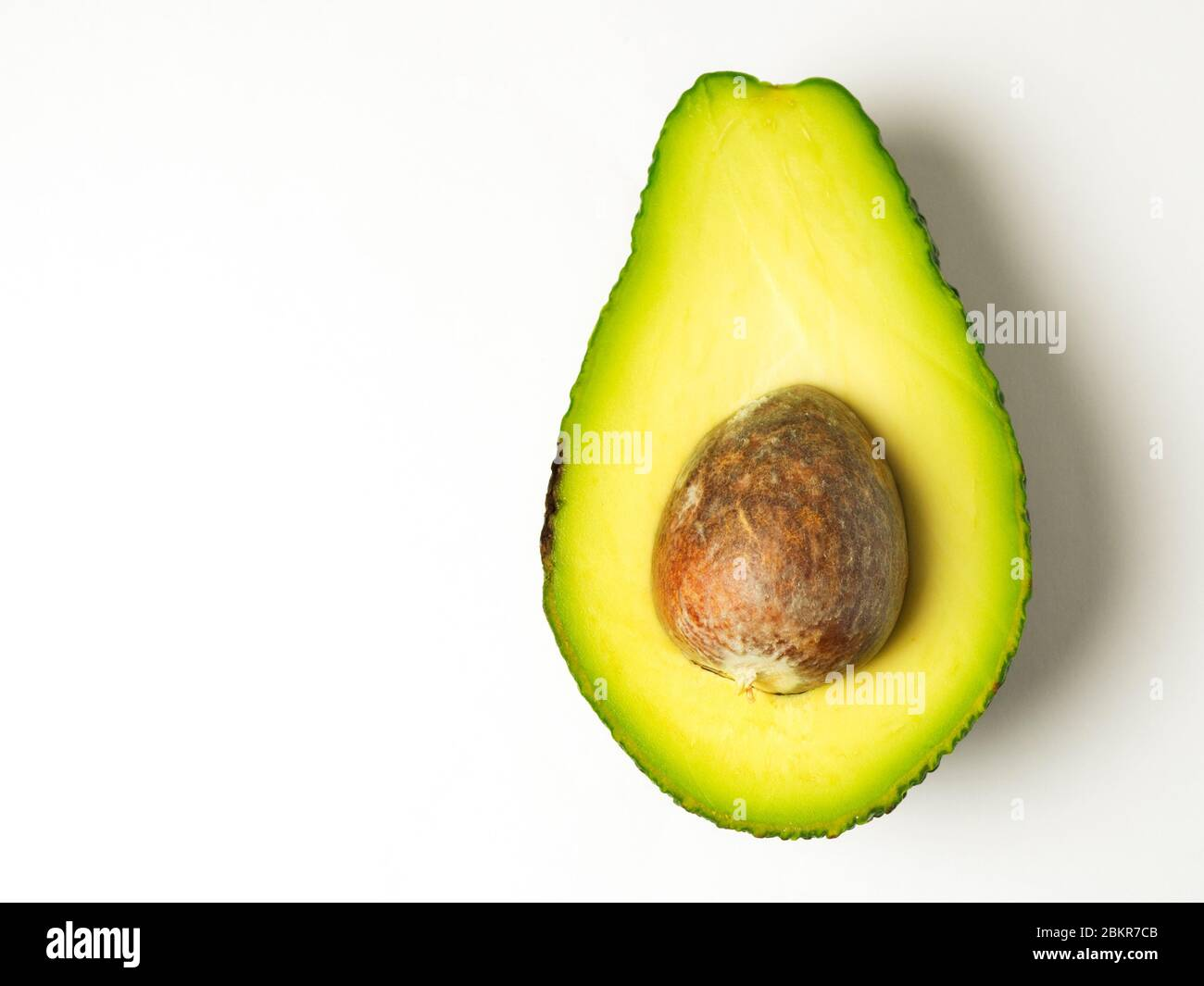 Half an avocado with the stone left in on a white background Stock Photo